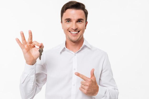 Porträt eines glücklichen lächelnden mannes im hemd, das schlüssel hält