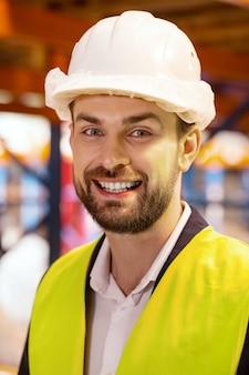 Porträt eines glücklichen lagerhausarbeiters, während er sie ansieht