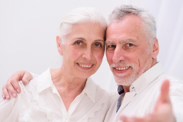 Porträt eines glücklichen liebevollen älteren paares, das kamera betrachtet