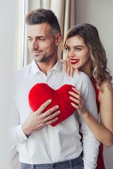 Porträt eines glücklichen liebevollen intelligenten gekleideten paarumarmens
