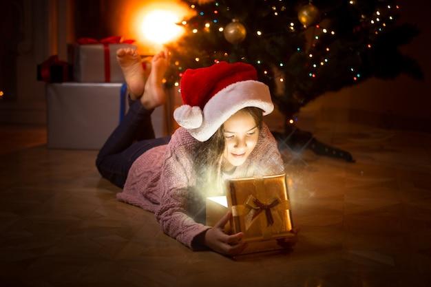 Porträt eines glücklichen mädchens, das auf dem boden liegt und in die magische gist-box schaut