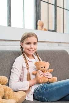 Porträt eines glücklichen mädchens, das auf dem grauen sofa hält den teddybären betrachtet kamera sitzt