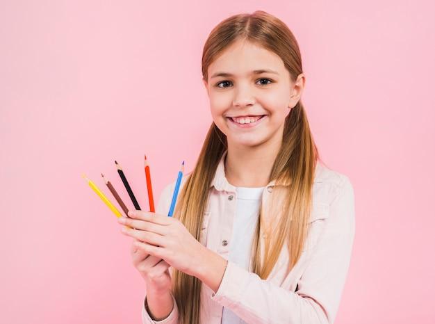 Porträt eines glücklichen mädchens, das in der hand farbige bleistifte schaut, die zur kamera gegen rosa hintergrund schauen