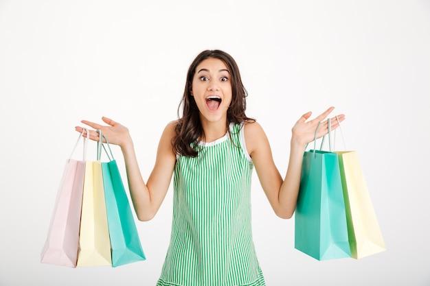 Porträt eines glücklichen mädchens im kleid, das einkaufstaschen hält