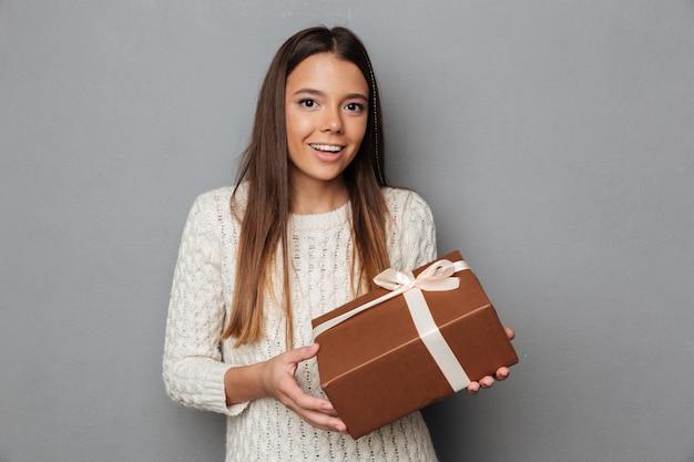 Porträt eines glücklichen mädchens im pullover, der geschenkbox hält