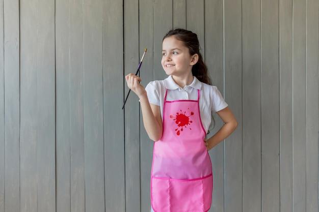 Porträt eines glücklichen mädchens im rosa schutzblech, das in der hand den pinsel weg schaut hält