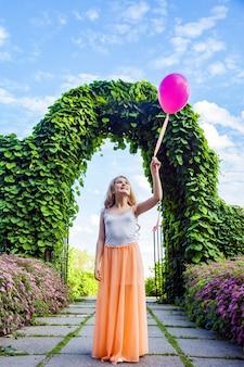 Porträt eines glücklichen mädchens mit luftballon, das im sommer im park genießt.