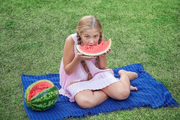 Porträt eines glücklichen mädchens mit wassermelone, die tagsüber den sommer im freien genießt.
