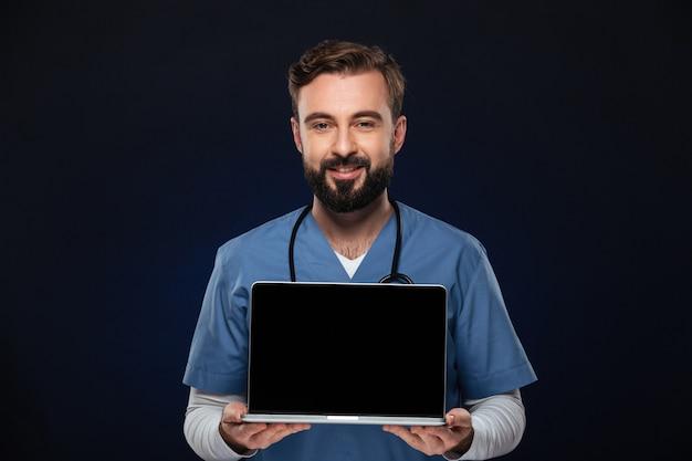 Porträt eines glücklichen männlichen doktors kleidete in der uniform an