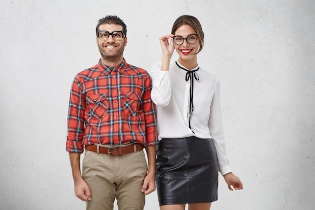 Porträt eines glücklichen männlichen nerds und seiner freundin, die froh sind, freizeit zusammen zu verbringen
