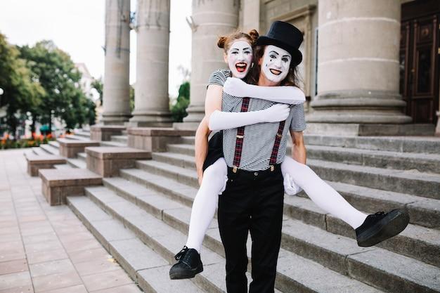 Porträt eines glücklichen männlichen pantomimen, der piggyback fahrt zum weiblichen pantomimen gibt