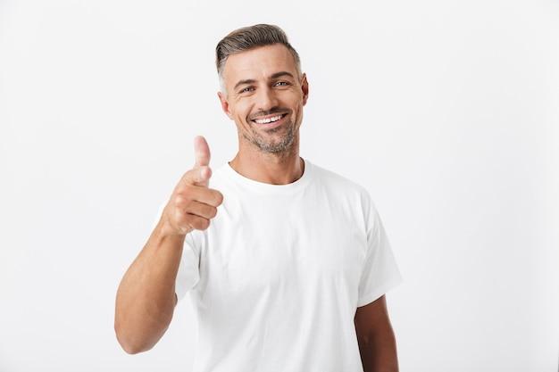 Porträt eines glücklichen mannes der 30er jahre mit borsten, der ein lässiges t-shirt trägt, das daumen nach oben isoliert auf weiß zeigt