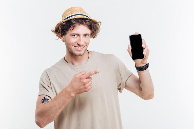 Porträt eines glücklichen mannes, der finger auf smartphone mit leerem bildschirm lokalisiert auf einem weißen hintergrund zeigt