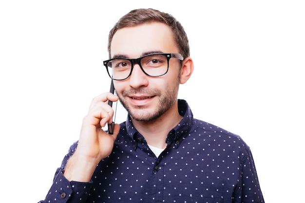 Porträt eines glücklichen mannes, der isoliert auf weißer wand telefoniert