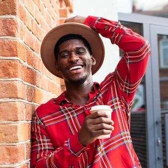 Porträt eines glücklichen mannes, der seinen hut hält