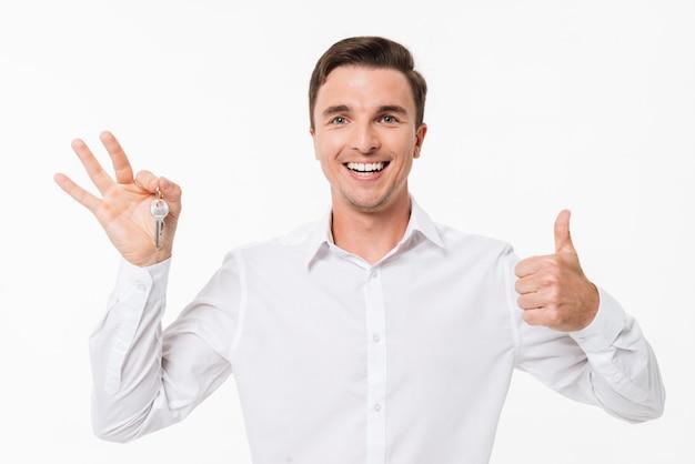 Porträt eines glücklichen mannes im weißen hemd, das schlüssel hält
