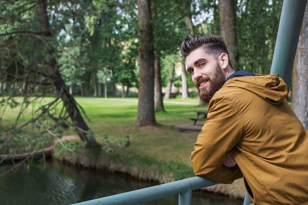 Porträt eines glücklichen mannes, lächelnd und genießen natur in der herbstzeit, nahe dem fluss.
