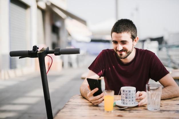 Porträt eines glücklichen mannes nahe bei einem e-roller