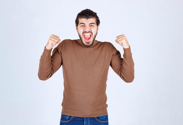 Porträt eines glücklichen modells des jungen mannes in erfolgreicher pose.