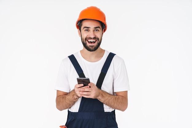 Porträt eines glücklichen positiven erbauers des jungen mannes in der helmaufstellung lokalisiert über weißer wand unter verwendung des handys.