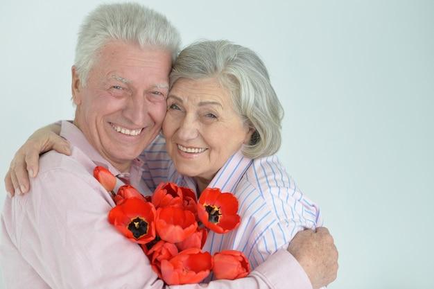 Porträt eines glücklichen reifen paares mit mohnblumen