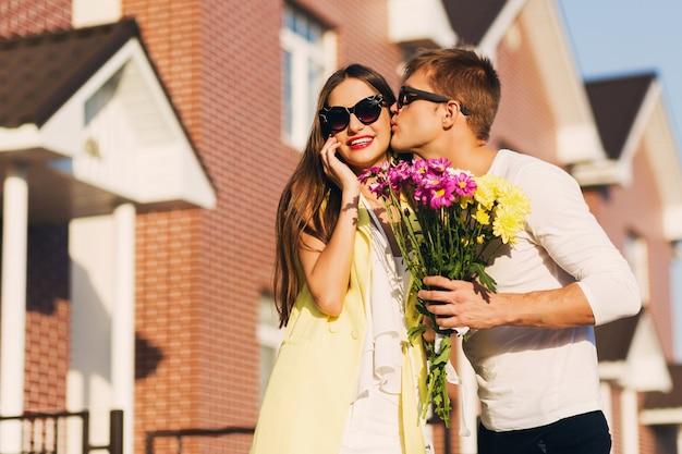 Porträt eines glücklichen romantischen paares, das am abend draußen in der europäischen stadt umarmt. junge hübsche frau, die blumen hält. paar in der liebe aus.