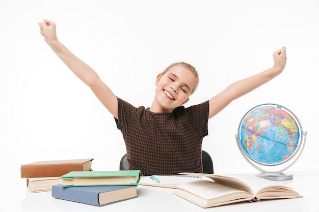 Porträt eines glücklichen schulmädchens, das bücher liest und hausaufgaben macht, während es am schreibtisch in der klasse sitzt, isoliert über weißer wand