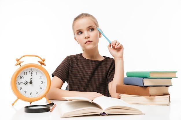 Porträt eines glücklichen schulmädchens mit großem wecker auf dem schreibtisch, das bücher in der klasse studiert und liest, isoliert über weißer wand