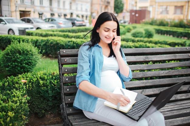 Porträt eines glücklichen schwarzen haares und der stolzen schwangeren frau im park. das weibliche model arbeitet am computer