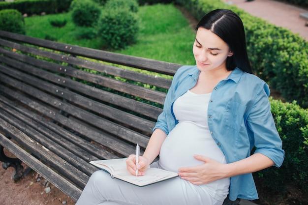 Porträt eines glücklichen schwarzen haares und der stolzen schwangeren frau im park. das weibliche model schreibt notizen in ihr notizbuch.