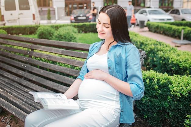 Porträt eines glücklichen schwarzen haares und der stolzen schwangeren frau in einer stadt in der straße. das weibliche modell liest ein buch