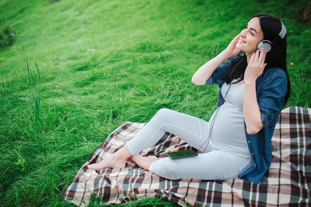 Porträt eines glücklichen schwarzen haares und einer stolzen schwangeren frau in einer stadt in einem park. die werdende mutter hört mit einem ungeborenen kind musik im park