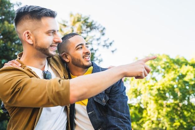 Porträt eines glücklichen schwulen paares, das zeit zusammen verbringt und ein date im park hat. lgbt und liebeskonzept.
