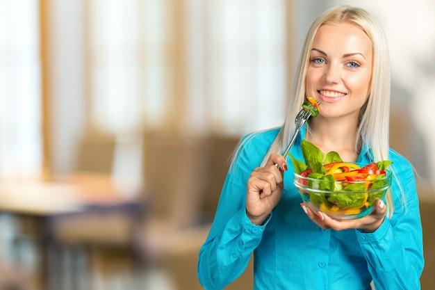 Porträt eines glücklichen spielerischen mädchens, das frischen salat von einer schüssel isst