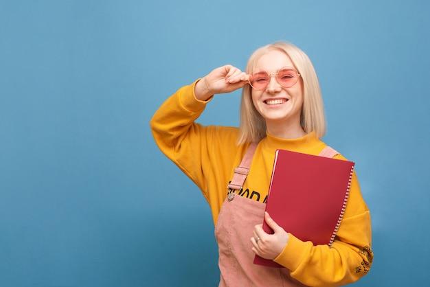 Porträt eines glücklichen studentenmädchens in rosa brille und einem notizblock in ihrer hand steht auf einem blau