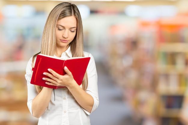 Porträt eines glücklichen studentenmädchens oder -frau mit büchern in der bibliothek