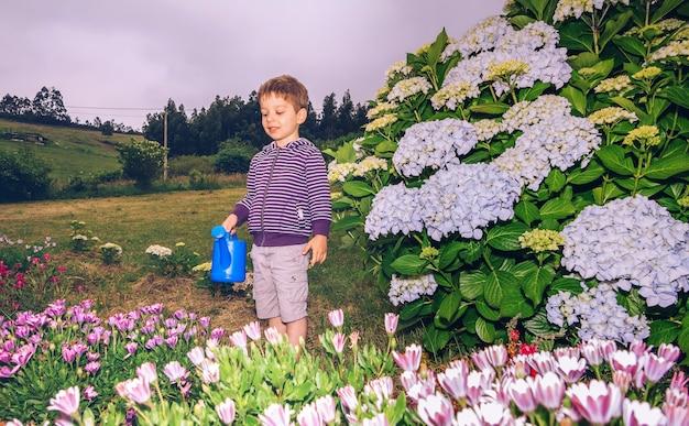 Porträt eines glücklichen süßen jungen, der blumen im garten mit einer blauen gießkanne gießt