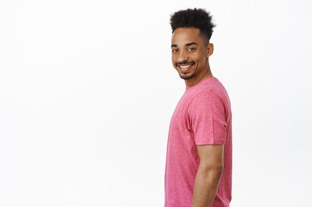 Porträt eines glücklichen und selbstbewussten afroamerikaners, der im profil steht, den kopf mit einem großen fröhlichen lächeln auf seinem gesicht dreht und in einem rosa t-shirt auf weiß steht