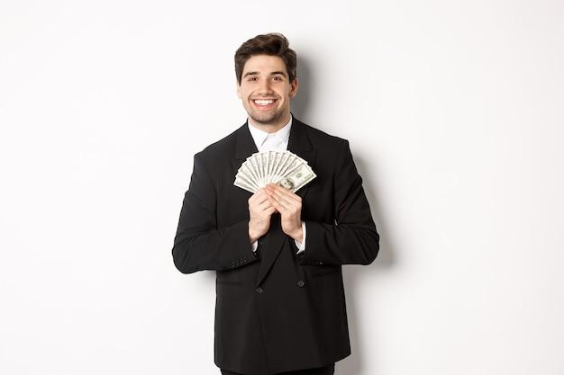 Porträt eines glücklichen und zufriedenen, gutaussehenden mannes im anzug, der geld umarmt und zufrieden aussieht und auf weißem hintergrund steht