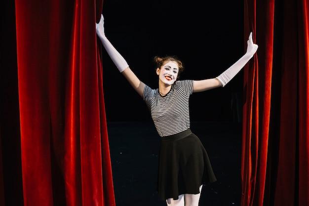 Porträt eines glücklichen weiblichen pantomimekünstlers, der roten vorhang hält