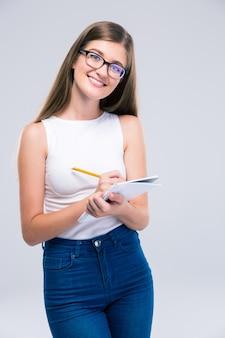 Porträt eines glücklichen weiblichen teenagers, der notizen im notizbuch lokalisiert schreibt