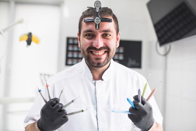 Porträt eines glücklichen zahnarztes mit verschiedenen zahnmedizinischen werkzeugen