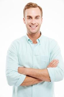 Porträt eines glücklichen zufälligen mannes, der mit verschränkten armen über der weißen wand steht und nach vorne schaut