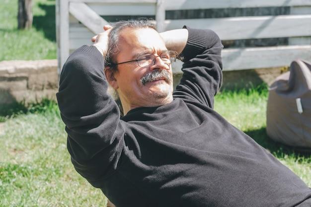 Porträt eines grauhaarigen erwachsenen reifen mannes mit brille und schnurrbart, der auf sitzsack sitzt und mit den händen hinter dem kopf lächelt