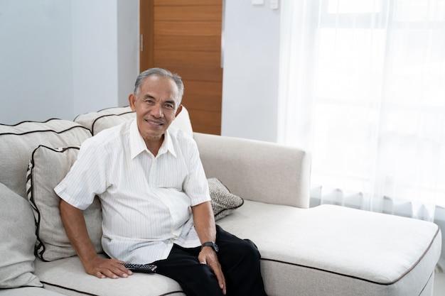 Porträt eines großvaters, der allein auf der couch sitzt