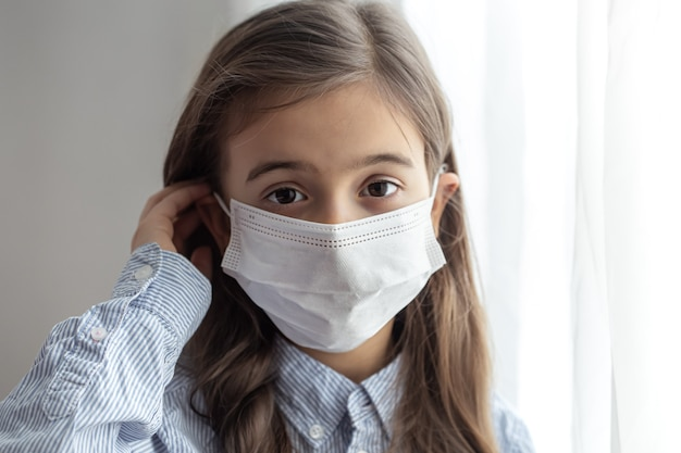 Porträt eines grundschulmädchens in einer einwegschutzmaske
