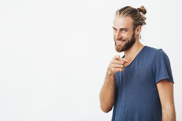 Porträt eines gut aussehenden bärtigen mannes mit großer frisur, die mit zeigefinger zeigt