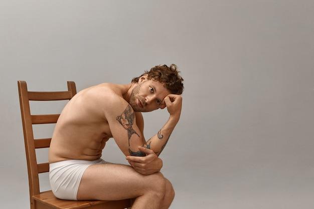 Porträt eines gut aussehenden bärtigen nackten mannes mit tätowiertem arm, der oben ohne auf holzstuhl sitzt und nur weiße boxershorts trägt.