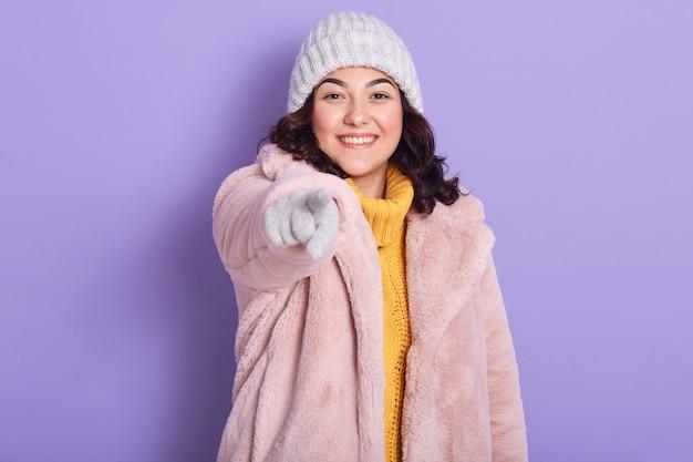 Porträt eines gut aussehenden positiven modells, das ihre hand ausstreckt