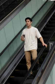 Porträt eines gutaussehenden asiatischen mannes, der draußen in der stadt kaffee trinkt